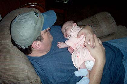 adoptive father lovingly holds his sleeping baby as he sits on the couch