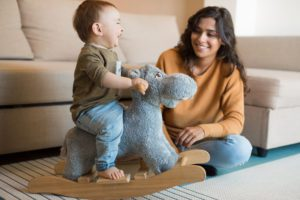 baby on rocking horse smiling with mom to illustrate How To Adopt A Baby With Lifetime Adoption